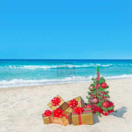 Christmas tree and golden gift boxes with big red bow on the sea