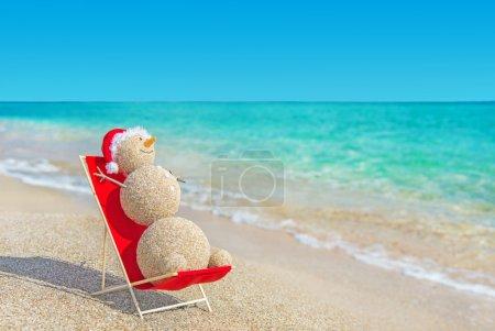 Sandy snowman in santa hat sunbathing in beach lounge.