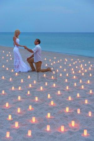 proposition à la plage de la mer en bougies contre le coucher de soleil