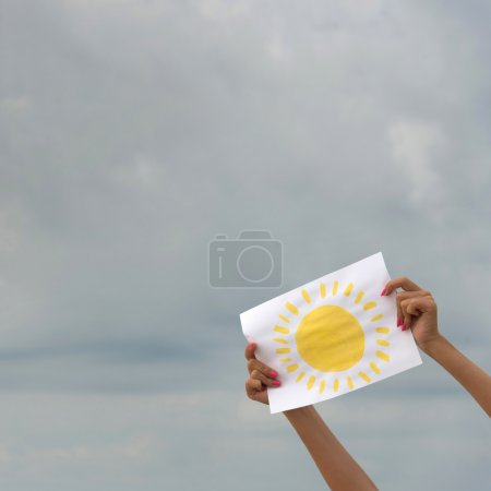 Photo for Human hands with sheet of paper with sun image against overcast sky - positive thinking concept - Royalty Free Image