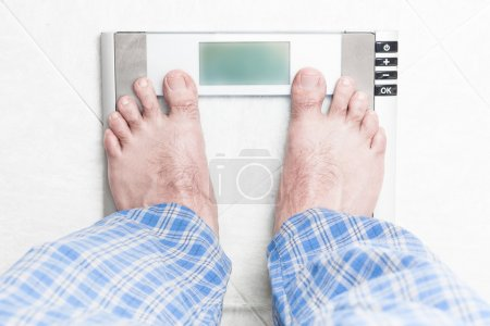 Young man standing on bathroom scale
