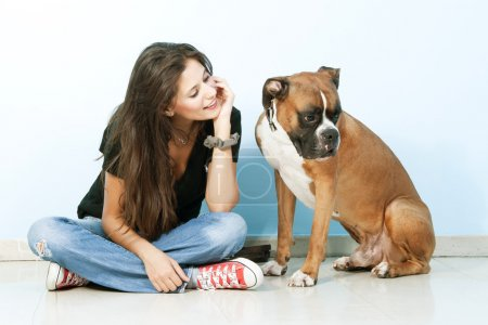 Young woman playing with her dog . Boxer dog.