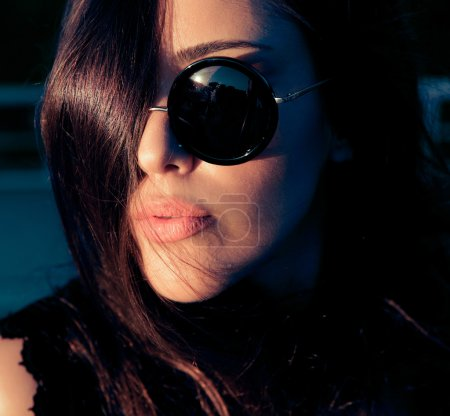 Mysterious woman in sunglasses , close up .