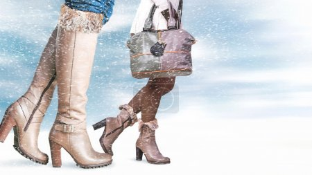 Photo for Female feet in winter shoes, snowfall in the foreground - Royalty Free Image