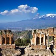 Ruins of the Greek Roman Theater with Etna eruptin...