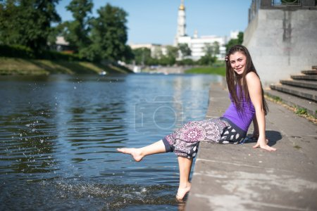 Photo for Girl sitting at the pier and hanging bare feet, water splashes - Royalty Free Image