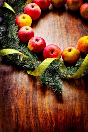 Christmas tree with apples and decorations on a wooden board
