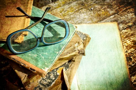 Photo for Close-up of opened book pages and glasses against vintage background. Vintage books with reading glasses in an used bookstore - Royalty Free Image