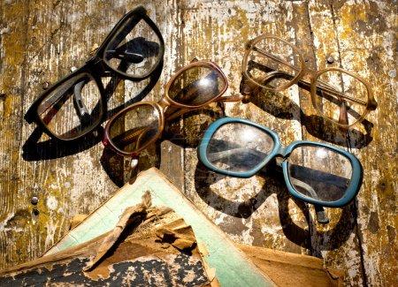Photo pour Gros plan des pages de livres ouvertes et des verres sur fond vintage. Livres anciens avec lunettes de lecture dans une librairie d'occasion - image libre de droit