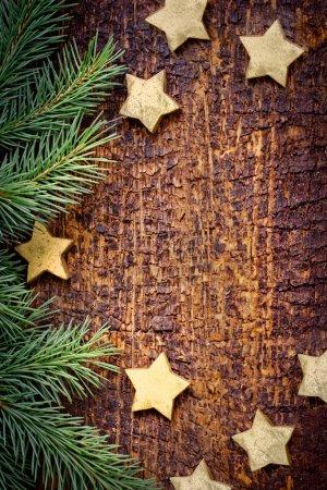 Foto de Textura navideña con ramas de pino y estrellas doradas sobre fondo de madera - Imagen libre de derechos