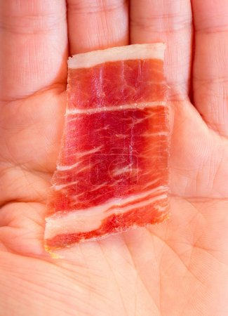 Photo for Top view of serrano ham slice over woman hand - Royalty Free Image