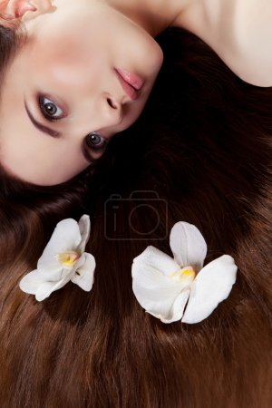 Photo for Beautiful girl lying on the floor with two white orchids in her long hair - Royalty Free Image