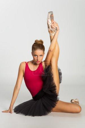 Photo pour Portrait de jeune belle danseuse porte jupe rouge dessus et noir tous-tous assis avec sa jambe vers le haut en pointes - image libre de droit