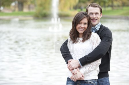 Young couple posing by the pond
