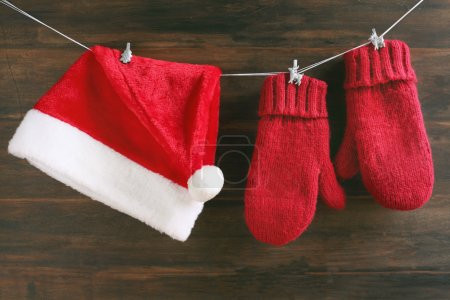 Photo for Christmas decoration with Santa cap and mittens on wooden background - Royalty Free Image