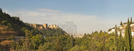 Panoramic photo of the Alhambra. Hill with trees. Blue cloudy sky. Granada. Andalusia. Spain.