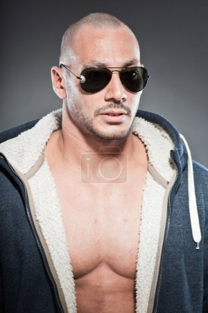 Muscled fitness man. Cool looking. Tough guy. Brown eyes. Bald. Wearing blue hoody shirt and sunglasses. Tanned skin. Studio shot isolated on grey background.