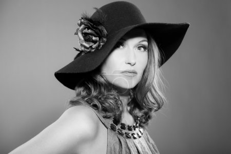 Photo for Glamour vintage black and white portrait of pretty woman with long hair. Wearing black hat with flower. Studio portrait isolated on grey. - Royalty Free Image