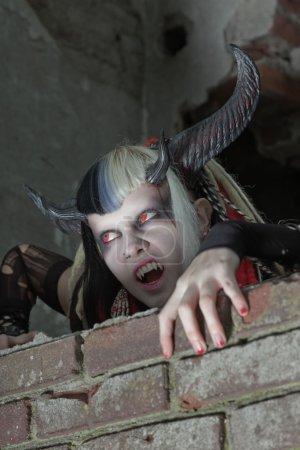 Foto de Aterrador demonio femenino hambre arrastrándose sobre la vieja pared de ladrillo sucio. - Imagen libre de derechos