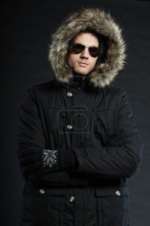 Photo for Handsome man dark winter fashion. Studio shot. Wearing black hoody jacket and sunglasses. - Royalty Free Image