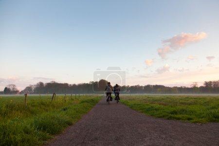 Photo pour Touristes à vélo sur la route à travers la prairie dans la brume au coucher du soleil . - image libre de droit