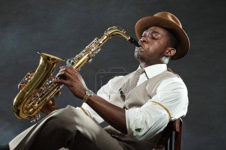 Photo pour Noir américain saxophoniste de jazz. Vintage. Studio tourné. - image libre de droit