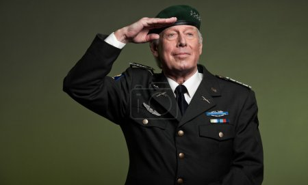 Military general wearing beret. Salutation. Studio portrait.