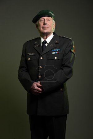Military general in uniform wearing beret. Studio portrait.