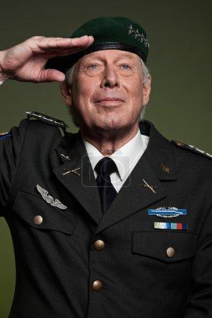 US military general wearing beret. Salutation. Studio portrait.