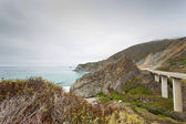 Coast of Big Sur with highway and cloudy sky. USA. California.