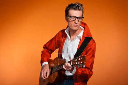Retro fifties musician with glasses playing accoustic guitar. St
