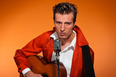 Retro fifties rock and roll singer playing accoustic guitar. Stu