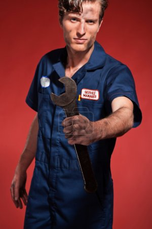 Retro fifties male car mechanic holding tool. Studio shot.