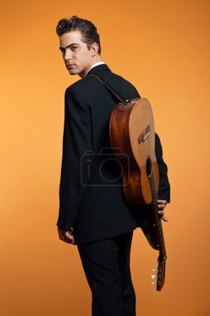 Photo for Retro country musician with guitar on is back wearing black suit. Studio shot. - Royalty Free Image