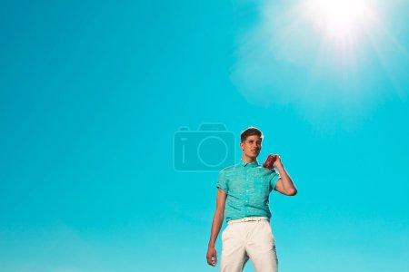 Retro fifties summer fashion man in blue shirt listens to portab