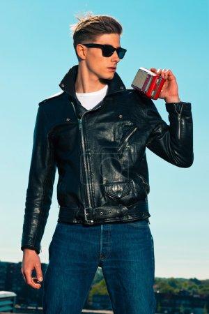 Rockabilly man retro 50s style with black jacket listens to port