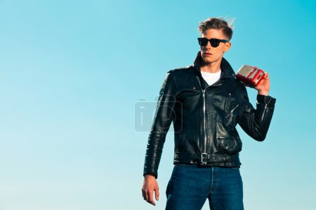 Photo for Retro fifties rockabilly man with black jacket listens to portable radio. Outdoor. Blue sky. - Royalty Free Image