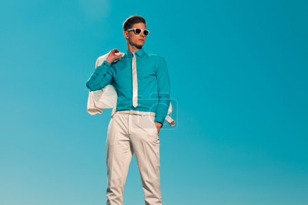 Photo for Retro fifties summer fashion man with white suit and sunglasses. Holding jacket. Blue sky. - Royalty Free Image