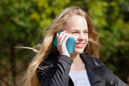 Young blonde girl with braces in park calling with mobile phone.