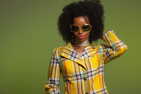 Photo for Dancing retro 70s fashion african woman with sunglasses. Yellow jacket and green background. - Royalty Free Image