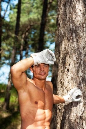 Shirtless muscled fitness man with working gloves in forest. Res
