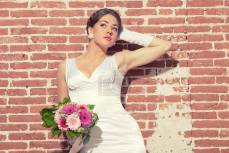 Vintage romantic sensual bride against old brick wall. Urban env