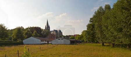 Panoramic landscape of meadow with church and trees and blue clo