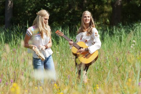 Two retro blonde 70s hippie girls making music with acoustic gui