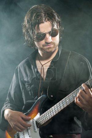 Photo pour Guitariste de rock psychédélique avec longs cheveux bruns et la barbe. lunettes de soleil. vêtus de noir. stade de fumée. - image libre de droit