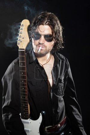 Photo pour Guitariste de rock avec longs cheveux bruns et de barbe et de lunettes de soleil habillés en noir. fumer une cigarette. - image libre de droit
