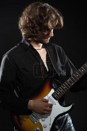 Photo pour Guitariste de rock psychédélique avec longs cheveux bruns et la barbe. vêtus de noir. - image libre de droit