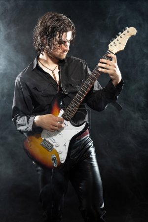 Photo pour Guitariste de rock psychédélique avec longs cheveux bruns et la barbe. vêtus de noir. stade de fumée. - image libre de droit