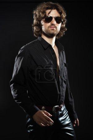 Photo pour Cool style rock danse musicien aux longs cheveux bruns et barbe. vêtus de noir. lunettes de soleil. - image libre de droit