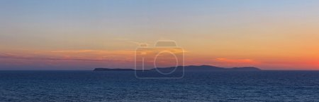 Panoramic shot of beautiful coastal sunset with some islands on